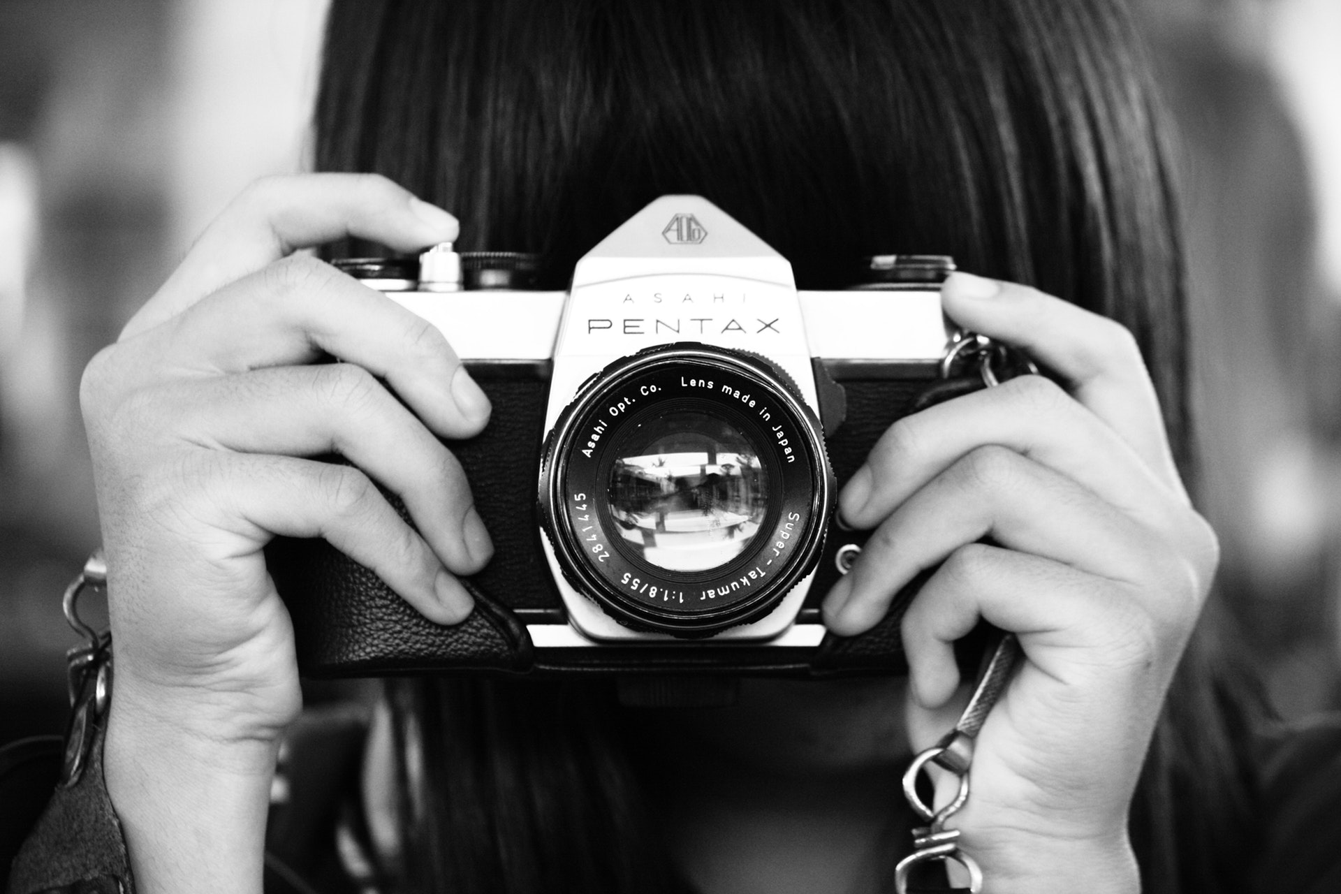 woman-holding-dslr-camera-in-grayscale-photography-707018